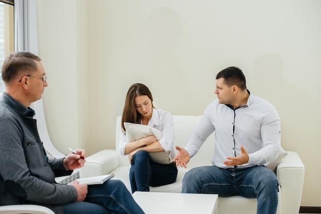 男性と女性の若い夫婦は、治療セッションで心理学者と話します。心理学。