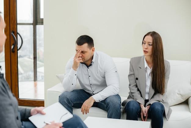 男性と女性の若い夫婦がセラピーセッションで心理学者と話します
