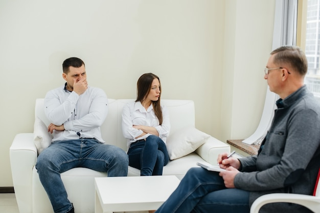 젊은 부부 남녀가 치료 세션에서 심리학자와 이야기합니다.