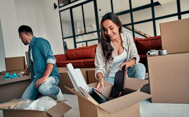 Молодая супружеская пара распаковывает вещи из ящиков в гостиной в доме. счастливые муж и жена веселятся, с нетерпением ждут нового дома. переезд, покупка дома, концепция квартиры.