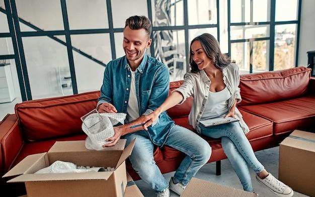 젊은 부부가 집 거실에 있는 상자에서 물건을 풀고 있습니다. 행복한 남편과 아내는 즐거운 시간을 보내고 있으며 새로운 가정을 기대하고 있습니다. 이사, 집 구입, 아파트 개념.