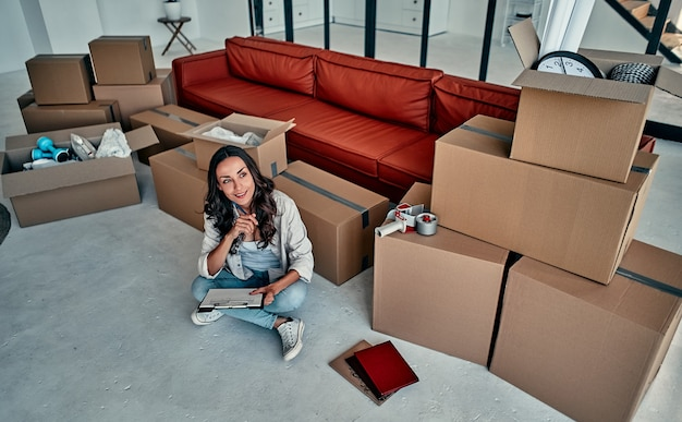 Молодая супружеская пара распаковывает вещи из ящиков в гостиной. переезд, покупка дома.
