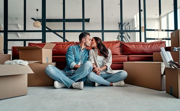 거실에 있는 상자에서 물건을 풀고 있는 젊은 부부 이사 집을 사다