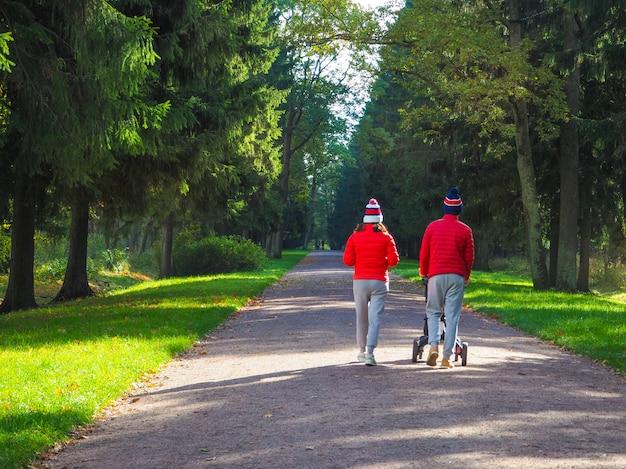 緑の路地を歩いているベビーカーを持つ若い夫婦。秋の公園の小道を歩く人々。