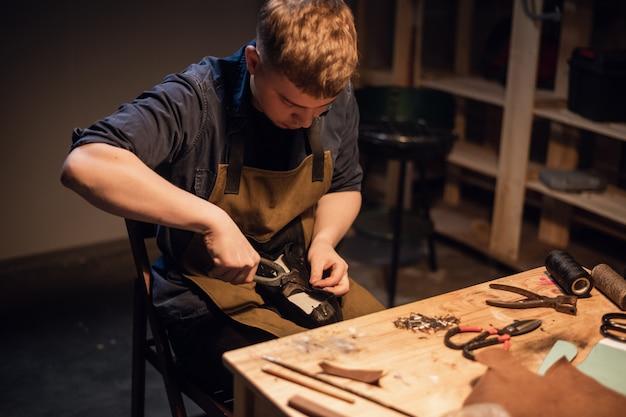 彼のワークショップで靴の手動生産の若いマスターは、靴の作成に取り組んでいます。
