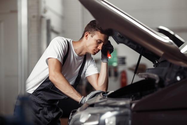 Молодой механик недоумевает, работая в автосервисе.