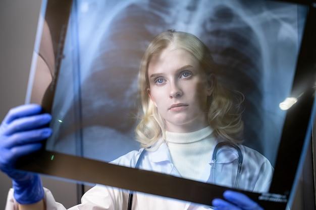 젊은 의료 노동자가 rentgens 사진을 봐