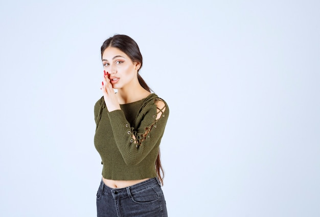 흰 벽에 비밀을 말하는 녹색 블라우스에 젊은 모델