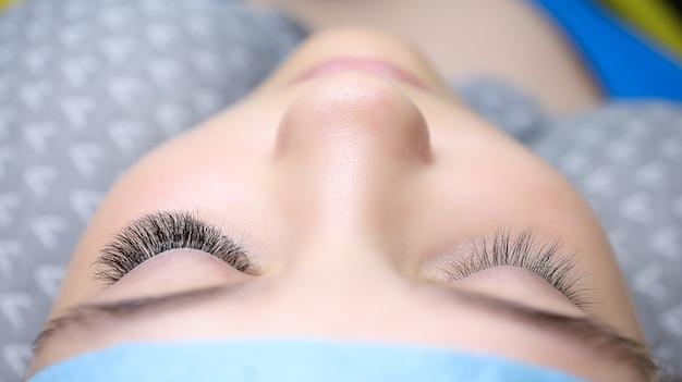 若いモデルが片方の目にまつげを伸ばした美容ソファに横たわっています。結果は左右の目の前です。