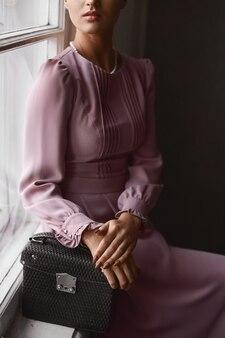 유행 지갑을 유지하고 빈티지 인테리어에서 포즈 핑크 이브닝 드레스에 젊은 모델 여자