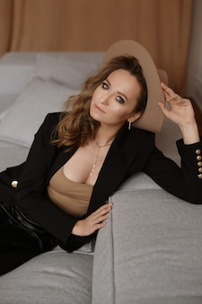 室内でポーズをとるトレンディな帽子に完璧なメイクと青い目をした若いモデルの女性