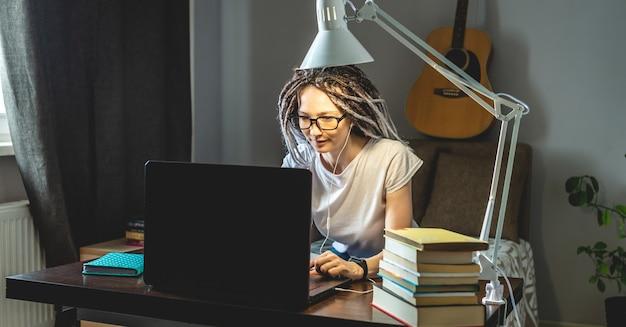 젊은 현대 여성 직원이 노트북을 사용하는 방에서 집에서 원격으로 온라인으로 작업하고 있습니다.