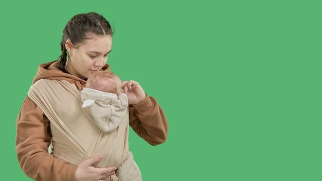 녹색 배경에 슬링에 작은 아기와 함께 젊은 현대 어머니