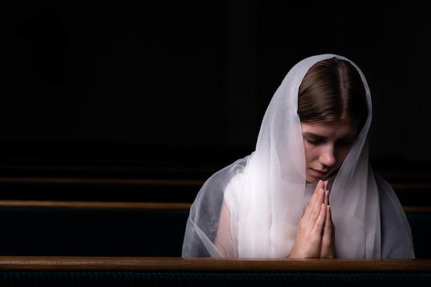 頭にハンカチをかけたささやかな少女が教会に座って祈っています。宗教、祈り、礼拝