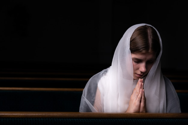 ハンカチを頭につけたささやかな少女が教会に座って祈っています。宗教、祈り、礼拝の
