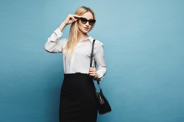 白いブラウスと黒のスカートに彼女のサングラスを調整し、分離された青の背景でポーズのモダンな若い女性