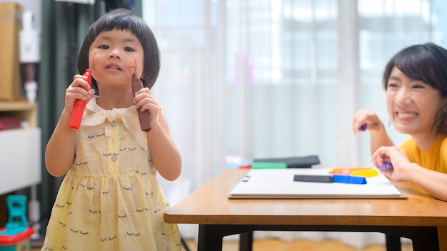 自宅の居間で色鉛筆で描く娘を助ける若いお母さん。
