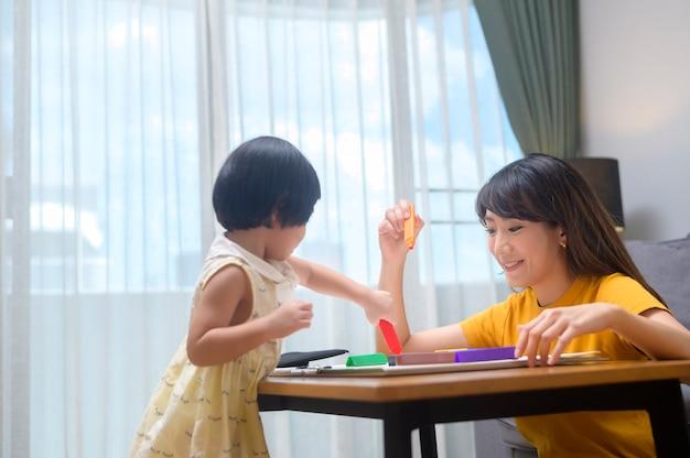 自宅の居間で色鉛筆で描く娘を助ける若いお母さん。 Premium写真