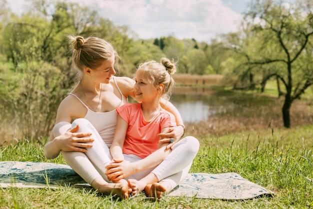 Молодая мама и дочь в спортивной одежде занимаются йогой вместе в парке