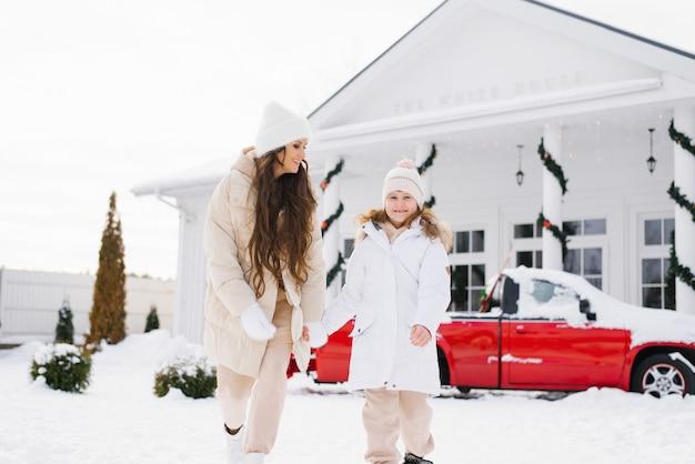 겨울옷을 입은 젊은 엄마와 딸이 손을 잡고 겨울 안뜰을 산책한다
