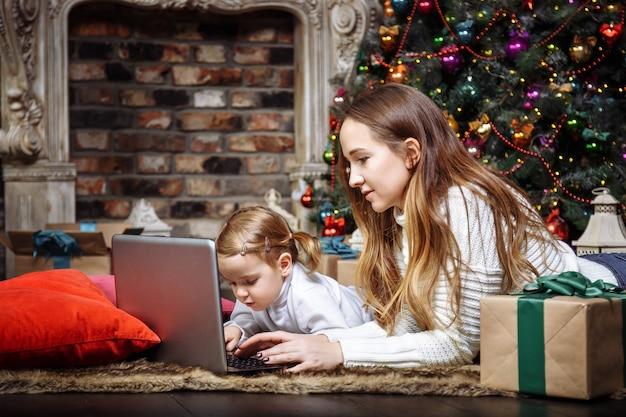 クリスマスツリーの近くに横たわっているラップトップを使用して若い母と娘