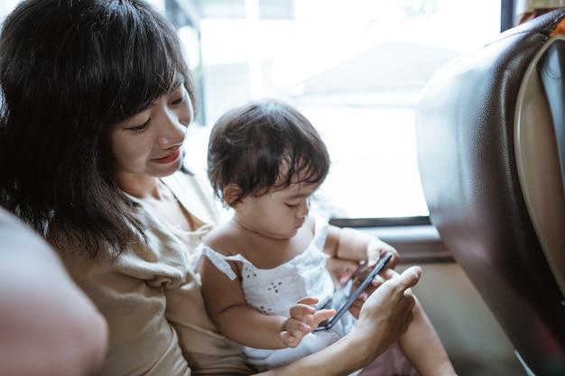 젊은 엄마와 어린 소녀가 여행하는 동안 버스에 앉아 휴대폰으로 비디오를 봅니다.