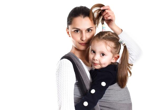 ベビーラップを編んだ若い母親と幼児の女の子。