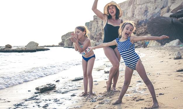 若い母親と2人の小さな娘が海岸で楽しんで、踊り、笑っています。休暇中の幸せな家族。