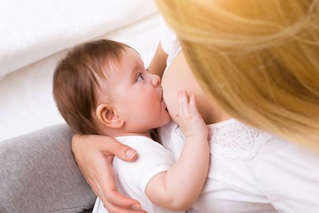 그녀의 팔에 안고 그녀의 작은 아기 소녀 모유 수유 젊은 어머니