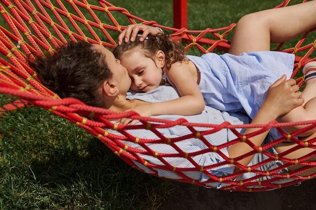 若い母親がハンモックに横になっている幼い娘を優しく抱きしめ、暖かい晴れた夏の日に自然のある場所で時間を楽しんでいます