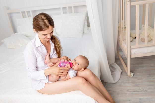 한 젊은 엄마가 6 개월 된 아기를 품에 안고 하얀 침대, 엄마와 아이의 사랑, 어머니의 날, 텍스트를위한 장소에 병에서 우유를 먹입니다.