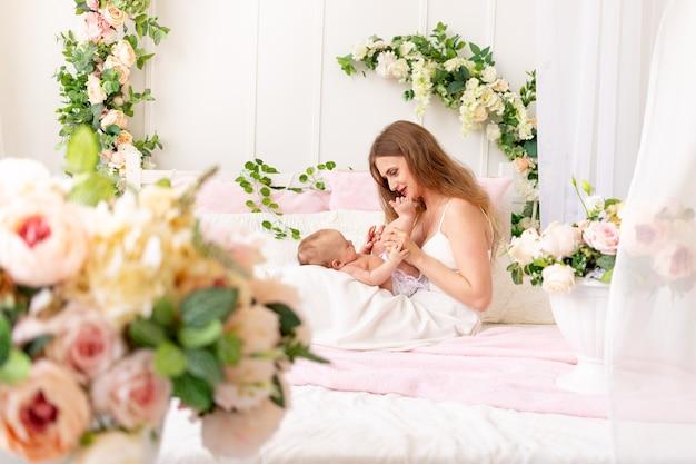 Молодая мама держит ребенка на руках и целует его ножки в красивом интерьере