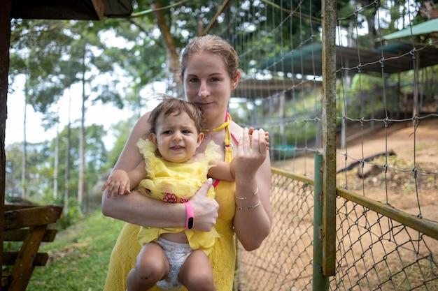 Молодая мама держит на руках симпатичного малыша и смотрит через сетку забора в зоопарке. копировать пространство.