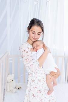 若い母親が生まれたばかりの赤ちゃんを抱きかかえて、ベビーベッドの近くの寝室で眠らせます。これは、母性と幸せな家族の概念です。