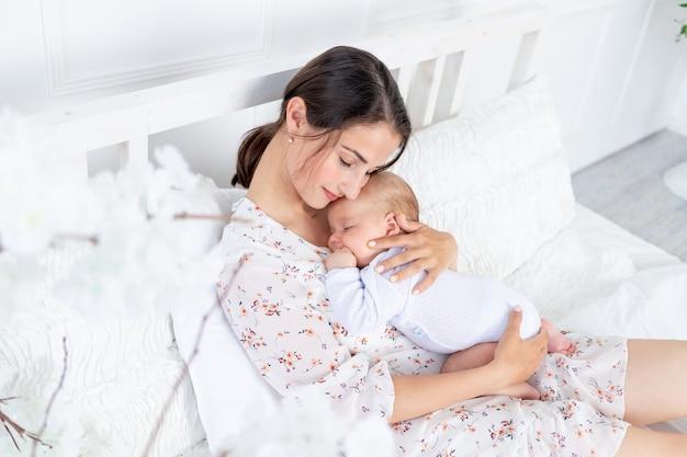 젊은 어머니는 침실에 있는 침대에서 잠든 신생아를 팔에 안고 있고, 모성 개념과 행복한 가족입니다.