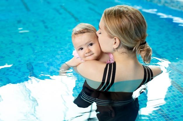 Молодая мама держит свою маленькую дочку в бассейне, обнимает ее и целует.