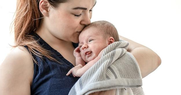 若い母親は、白い背景の上に、彼女の生まれたばかりの息子を腕に抱き、キスをします。