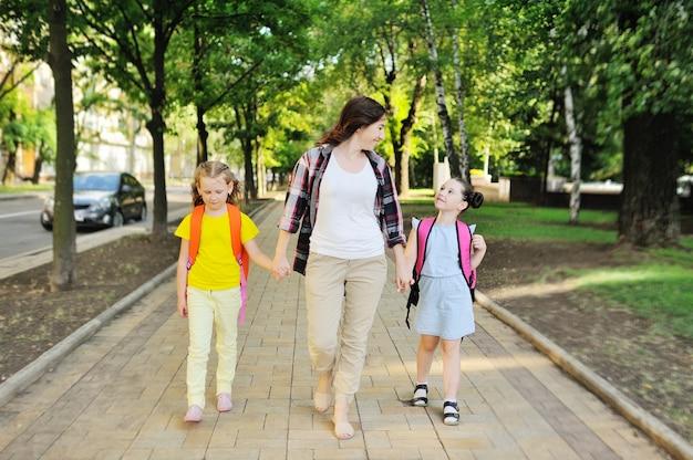 Молодая мать в клетчатой рубашке ведет в школу двух дочерей со школьными рюкзаками, держась за руки. снова в школу, образование, день знаний.