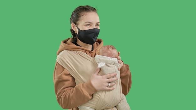 녹색 배경에 슬링에 작은 아기와 함께 천 마스크에 젊은 어머니