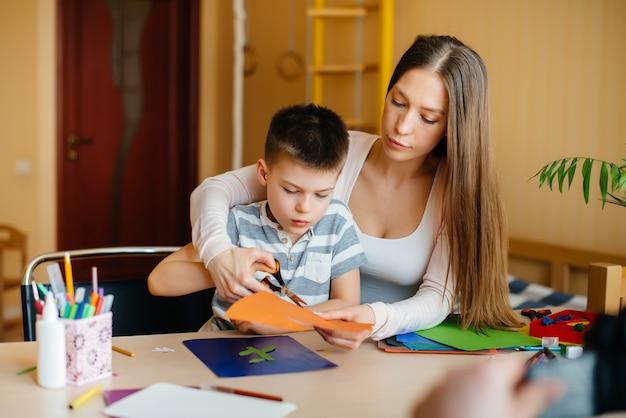 Молодая мать делает домашнее задание с сыном дома. родители и обучение