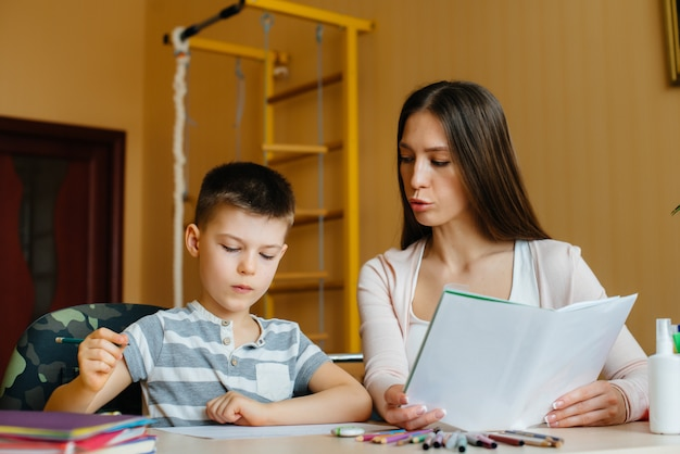 Молодая мать делает домашнее задание с сыном дома. родители и обучение.