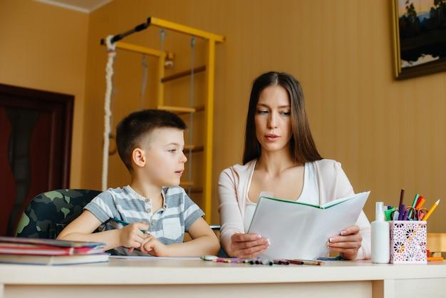 Молодая мама делает уроки с сыном дома. родители и обучение.