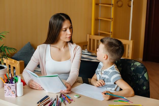 젊은 어머니는 집에서 그녀의 아들과 함께 숙제를하고있다