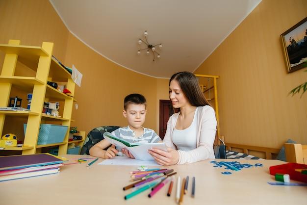 若い母親が息子と一緒に家で宿題をしている