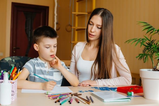 젊은 엄마가 집에서 아들과 함께 숙제를하고있다