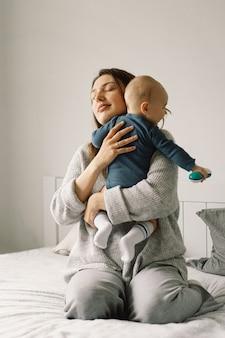 若い母親が小さな男の子と遊んでいます。授乳中の赤ちゃんの母親。幸せな母性。家族は家にいます。幸せな母と子のポートレート。