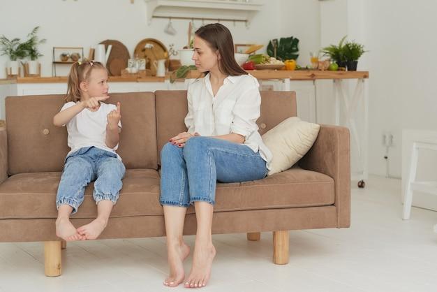 Молодая мама разговаривает со своим ребенком по душам. психолог общается с маленькой девочкой дома.