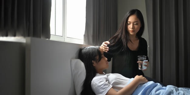 若い母親が寝室で病気の娘の世話をしています。