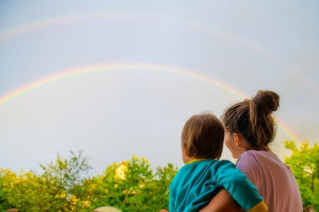 若い母親は赤ん坊を腕に抱えて空を見上げ、雨の後の虹を賞賛し、夏は屋外です。幸せなお母さんとかわいい笑顔の女の子。肯定的な人間の感情、