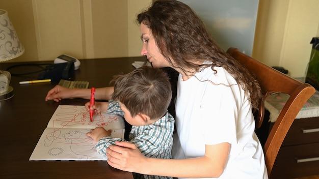 若い母親は子供と一緒にフェルトペンで絵を描きます。